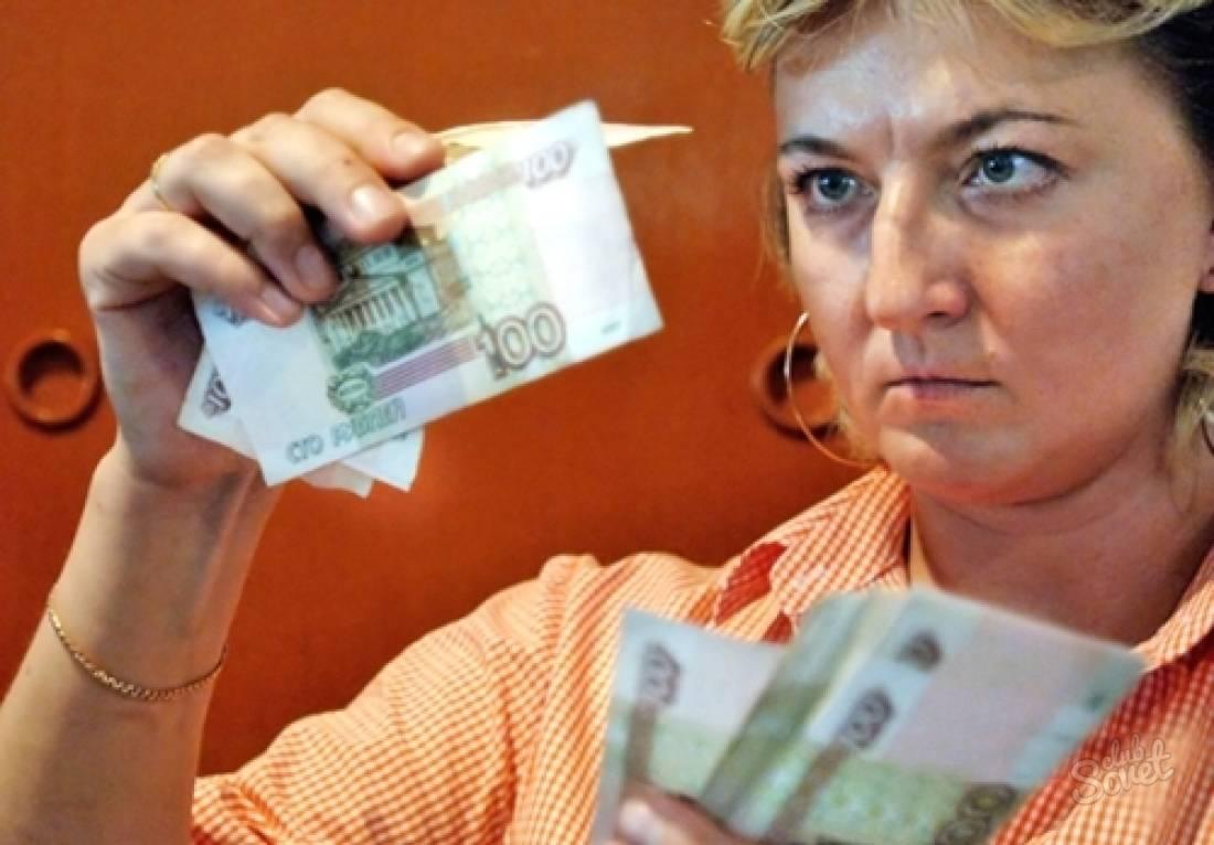 женщина проверяет деньги на подлинность